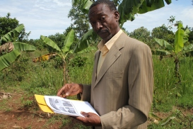 Charles Mulamata surveys a plot of land where he hopes to build an aquaponics facility.